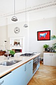 Free-standing island counter with sink and gas hob in grand interior with stucco ceiling frieze