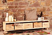 Selbst gebautes Sideboard mit Weinkiste als Stauraum vor Natursteinwand