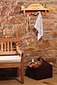 Shelf with hooks upcycled from old wine crate above bench and bag of firewood against rustic stone wall