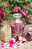 Dried rose petals of different colours in storage jars