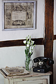 Old telephone and flowers on small table against half-timbered wall