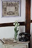 Altes Telefon und Blumen auf einem Tischchen vor Fachwerkwand
