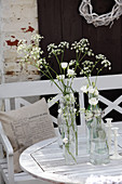 Wildflowers and eustomas in old swing-top bottles on table