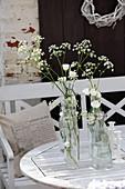 Wiesenblumen und Japanrosen in alten Bügelflaschen auf dem Tisch