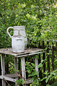 Stoneware pot and jug on old table next to fence in garden