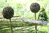 Garden sign on DIY fence with wicker balls on stakes