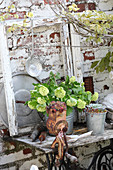 Ornaments on old sewing machine table against garden wall