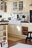 Cremefarbene Einbauküche mit Kassettentüren und grossem Aufsatzspülbecken aus Keramik