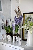 Shabby chic arrangement on white cabinet; spring flowers in glass vessels and enamel can, gilt-framed engraving and letters reading SPRING