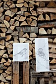 Hand-crafted paper lampshades with drawing of birds on table in front of stacked firewood