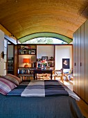 Bedroom with checked bedspread on double bed below wood-clad barrel-vaulted ceiling: antique wooden table and bookcases in background