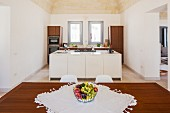 View across dining table with bowl of fruit on white lace mat to open-plan kitchen with wooden cupboards and island counter