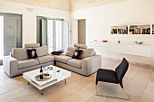 Pale sofa set in living room with tiled floor and interior folding shutters in Apulian holiday home