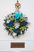 Blue and green fake flower Christmas wreath with baubles and chiffon bows on a white front door