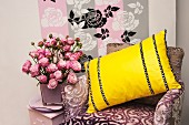 A purple velvet chair with a yellow cushion, vase of pink roses and a stencil background