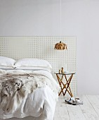 Bed with perforated panel as headboard