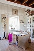 Korbstühle um einen runden Tisch und Shabby Deko mit alter Schneiderpuppe, romantisch gerahmten Fotos und Vitrinenschrank