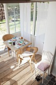 Set breakfast table and wicker chairs in sunny conservatory extension with untreated wooden floor