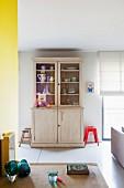 Vitrinen Küchenschrank im Vintagelook mit Geschirr in offener Appartementküche