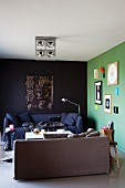 Lime green, artistically decorated wall next to black wall and two comfortable sofas in corner of apartment