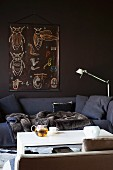 Cosy blanket on comfortable, dark grey sofa against brown wall and teapot on white coffee table