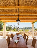 Long wooden table and wicker chairs on terrace below pergola with bamboo roof and view into summery, Mediterranean landscape
