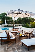 Antique-style, outdoor chairs with white cushions below parasol and pool in background in Mediterranean garden