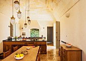 Dining table below pendant lamps with pine-cone-shaped lampshades hanging from vaulted ceiling and open-plan kitchen area in Mediterranean country house