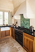 Corner kitchen counter with wooden base units and integrated gas cooker below masonry extractor hood