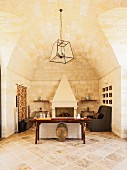 Sparsely furnished interior with open fireplace below vaulted ceiling