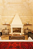 Ethnic tablecloth on surface in front of open fireplace in sparsely furnished interior with stone walls and vaulted ceiling