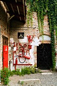 Corner of house in former factory with artistic installation of red-painted tools on brick wall