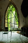 Chess table and delicate metal chairs in front of pointed arch with artistic, lattice-frame door with view into garden