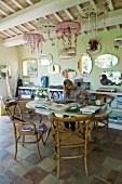 Frau am Tisch arbeitend mit Spiegelsammlung an der Wand und Traumfänger von Holzdecke abgehängt
