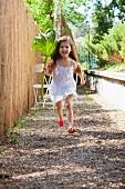 Kleines Mädchen läuft mit Rhabarberblatt neben Gartenzaun