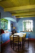 Rustic dining area in Mediterranean country house with blue marbled walls combined with antique lattice windows