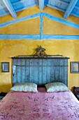 Contrasting colours and styles; wooden ceiling painted pale blue and marbled, ochre walls as backdrop for stained headboard of double bed