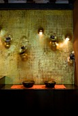 Bowls on black sideboard against artistically decorated wall with integrated water spouts, vases and sconce lamps