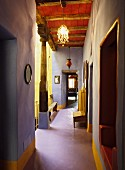 Unusual colour scheme in historical country house with lavender corridor walls, yellow accents and wooden ceiling painted Venetian red