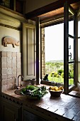 Bowls of lemons and vegetables on tiled sink unit in Tuscan, vintage kitchen; wide view through open window
