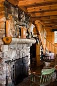 Holzstuhl vor Natursteinkamin Kamin und Tiertrophäen auf dem Sims in rustikaler Hütte