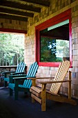The porch of an Adirondacks cabin with Adirondack chairs