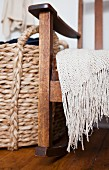 A knitted throw on a rocking chair and a woven laundry bask