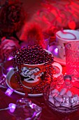 String of red beads in teacup next to glass bonbonniere on red velvet cloth