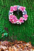Wreath of pink orchid flowers on mossy background above autumn leaves