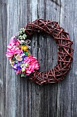 Wicker wreath with multicoloured flowers on wooden wall