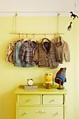 Improvised child's coat rack above chest of drawers