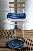 Still-life arrangement of plates on decking tiles in front of stacked towels on folding chair and white-painted metal barrels