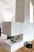 Firewood in designer, cubic, open fireplace in light-flooded attic studio