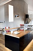 Black, glossy kitchen counter with breakfast bar and wooden worksurface in open-plan, attic interior
